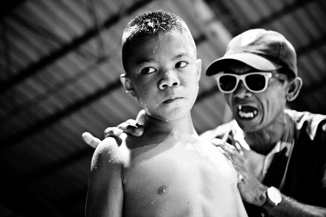 El entrenador le grita a un niño durante el descanso de la lucha.